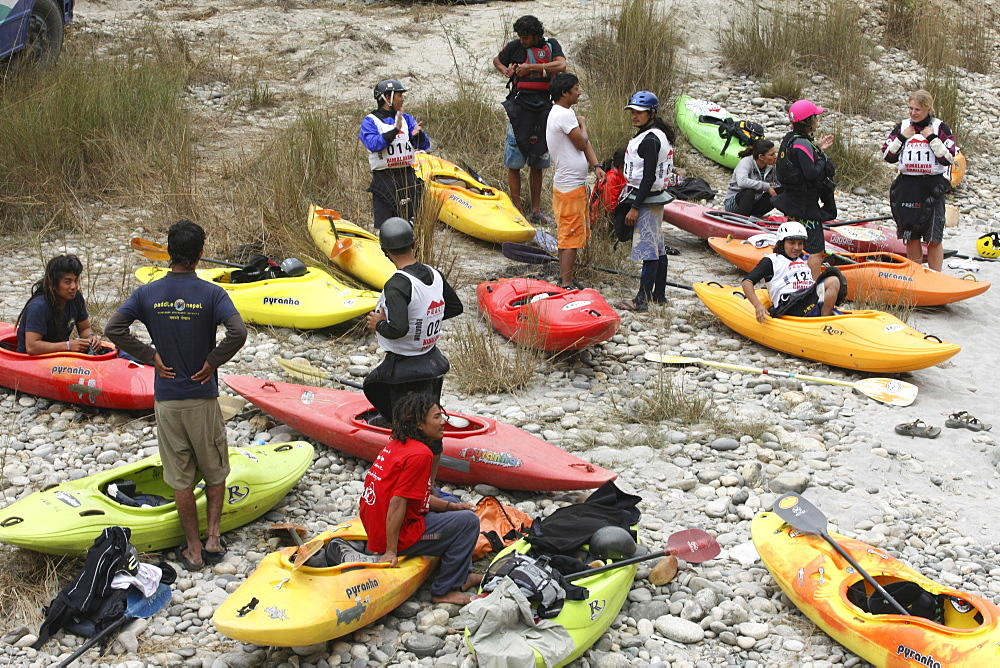 Paddlers carry their kayak to the start point for Downriver challenge. Trisuli, Nepal