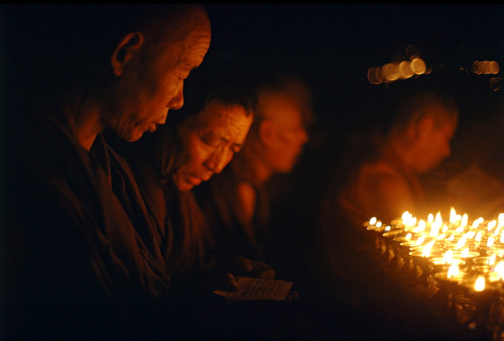 Monks offer butter lamps. Kalachakra initiation, bodhgaya. India. Monks attending kalachakra initiation at mahaboudhi temple in bodhgaya, india. mahabodhi temple marks site of buddhas enlightment twenty-five hundred years. centuries have made pilgrimages across himalayas to sites connected with life of historical buddha. From a tantric perspective, pilgrimage is more than paying homage at sacred sites. Rather, it is that activities performed at these places become a memory of place itself. By attuning oneself through ritual meditation to this timeless presence, similar experiences be evoked