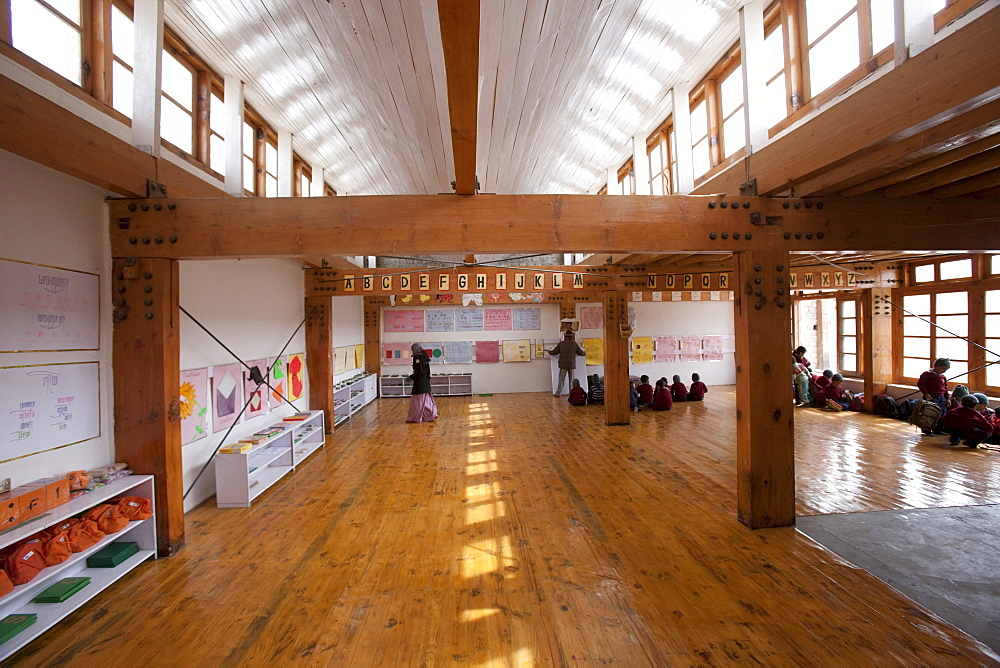 A light-filled elementary classroom. A white ceiling reflects light from the windows above. Traditional building methods and materials, such as the poplar and willow ceilings are combined with modern solar and passive solar technology. Druk Padma Karpo Institute. Shey, Ladakh, India