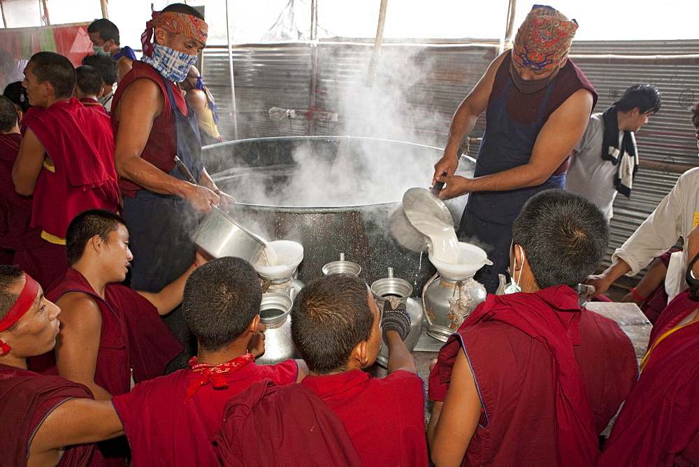 Volunteer monks make tibetan butter salt milk tea in gigantic vessel for the kalachakra initiation attendants. Kalachakra initiation in bodhgaya, india