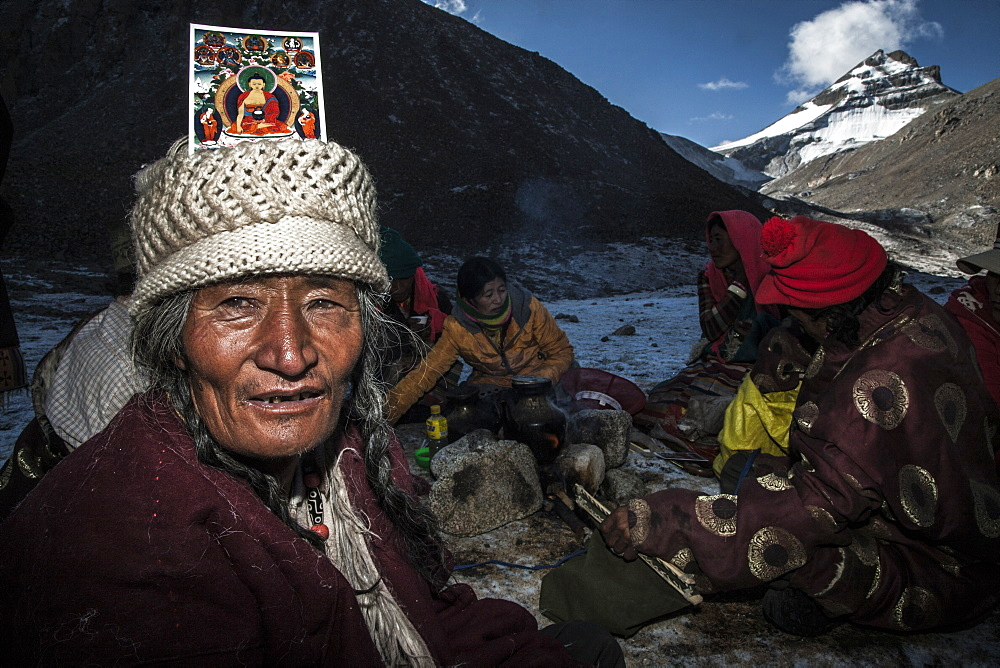 Pilgrim with a Buddha card on head at Dirapuk over Zutul Puk, Tibet, China, Asia