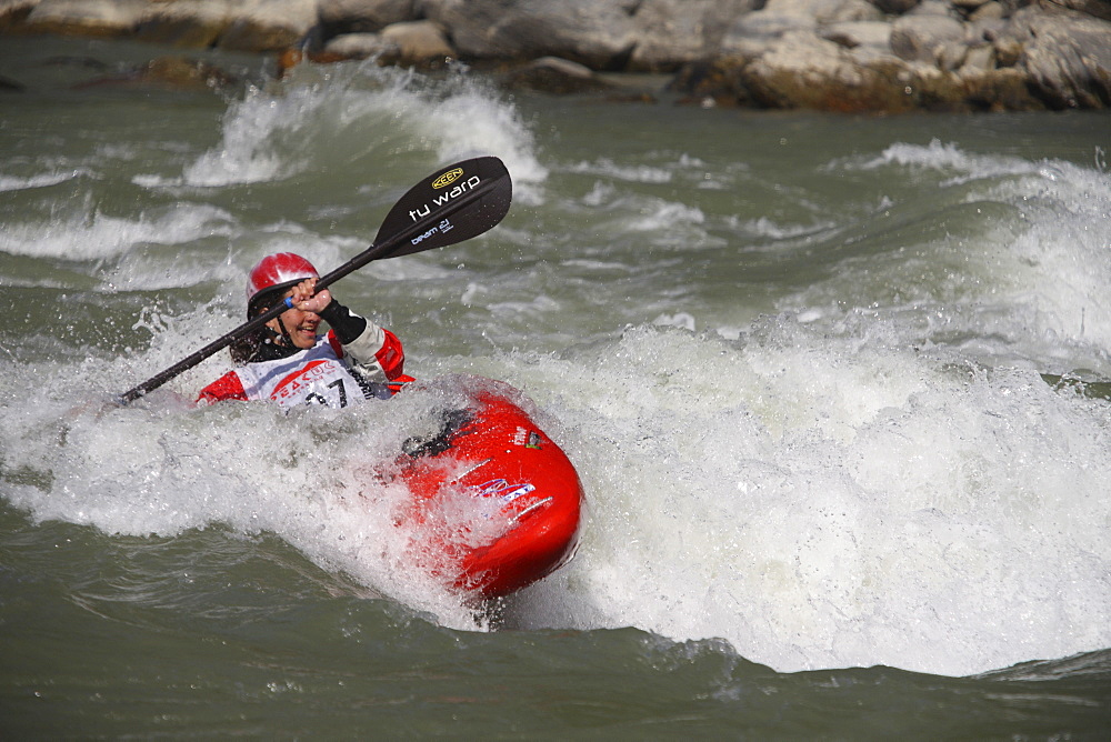 Paddler performing freestyle routines on a set wave. Trisuli, Nepal