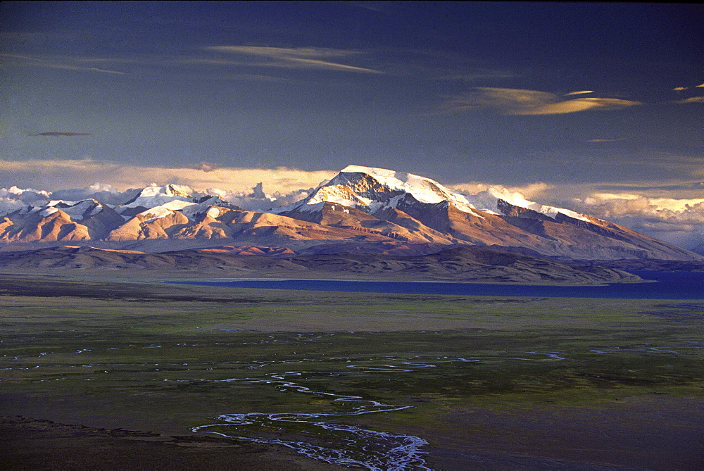 Gurla mandata. Tibet. barkha plain stretches as clouds light gather above bonpo mountain tagri trawo, tiger-striped mountain, known on english maps by sanskrit name, gurla mandhata with rakshas glittering beyond expanse of pilgrim tents