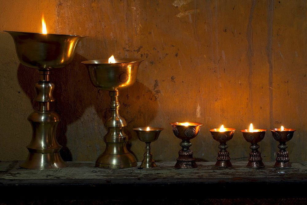 Butter lamps offering inside gompa of Leh Palace. Ladakh, India