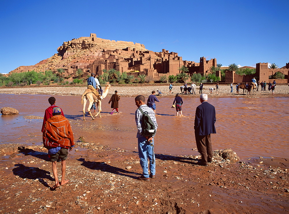Tourists cross river Asif Mellah to visit Kasbah Ait Ben Haddou, UNESCO World Heritage Site, near Ouarzazate, Morocco, North Africa, Africa