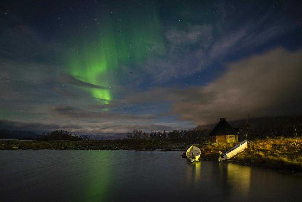 Aurora borealis over lake with boats and Kota, Kilpisjarvi, Northwest Finland, Lapland, Finland, Scandinavia, Europe