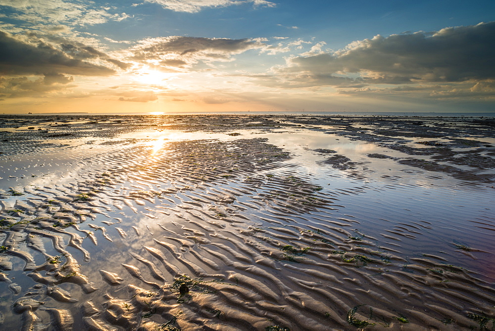 View of sandy beach and pools at low tide, at sunset, Reculver, Kent, England