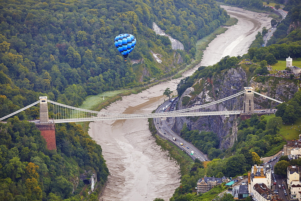A hot-air balloon flying over Clifton Suspension Bridge, an icon of Bristol, during the Bristol International Balloon Fiesta, Bristol, England, United Kingdom, Europe