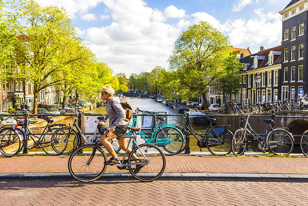 Cyclist riding over a bridge over Prinsengracht Canal, Amsterdam, Netherlands, Europe