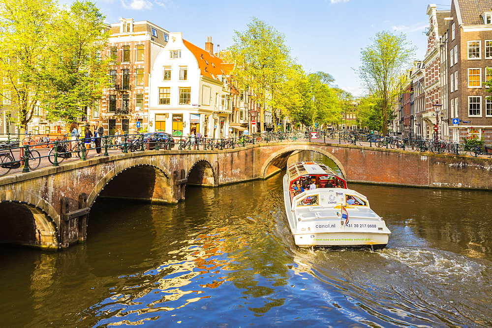 A boat going under a bridge over the Keizersgracht Canal, Amsterdam, Netherlands, Europe
