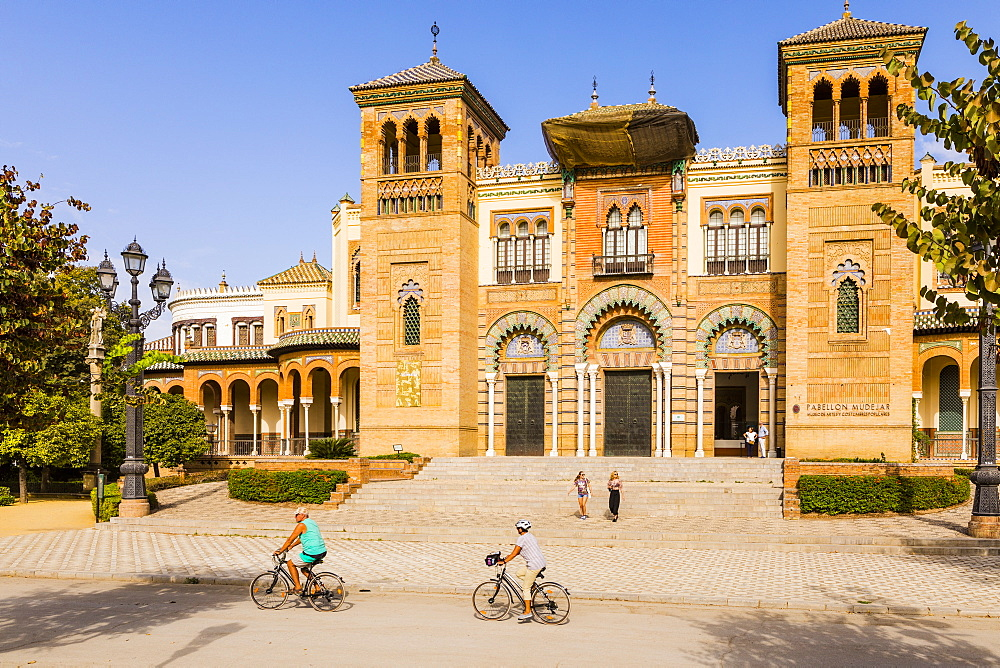 People riding bikes in front of the Museum of Popular Arts and Traditions in Maria Luisa Park, Seville, Andalusia, Spain, Europe