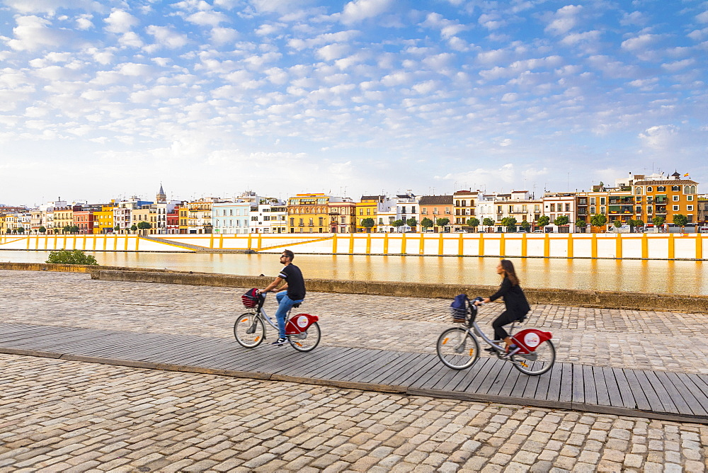 People cycling by the river Rio Guadalquivir, with Triana district in the background, Seville, Andalusia, Spain, Europe - 1207-230