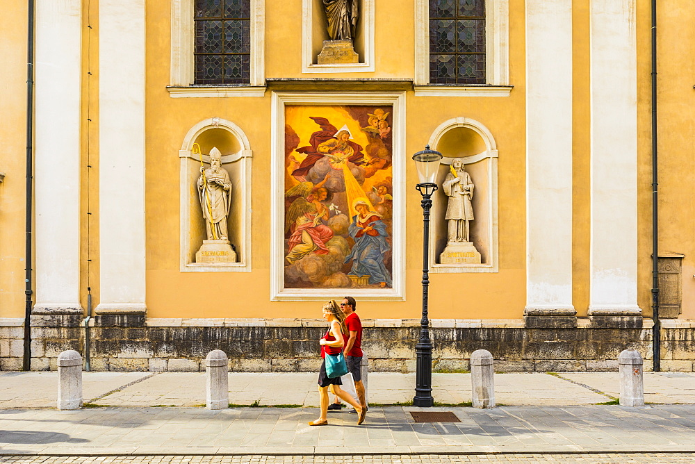 A couple walking in front of Saint Nicholas Cathedral, Ljubljana, Slovenia, Europe