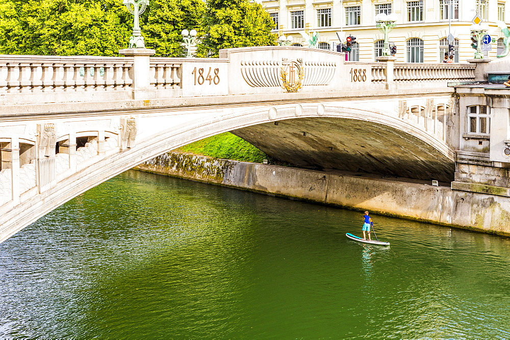 A boy paddle-boarding under Dragon Bridge, Ljubljana, Slovenia, Europe