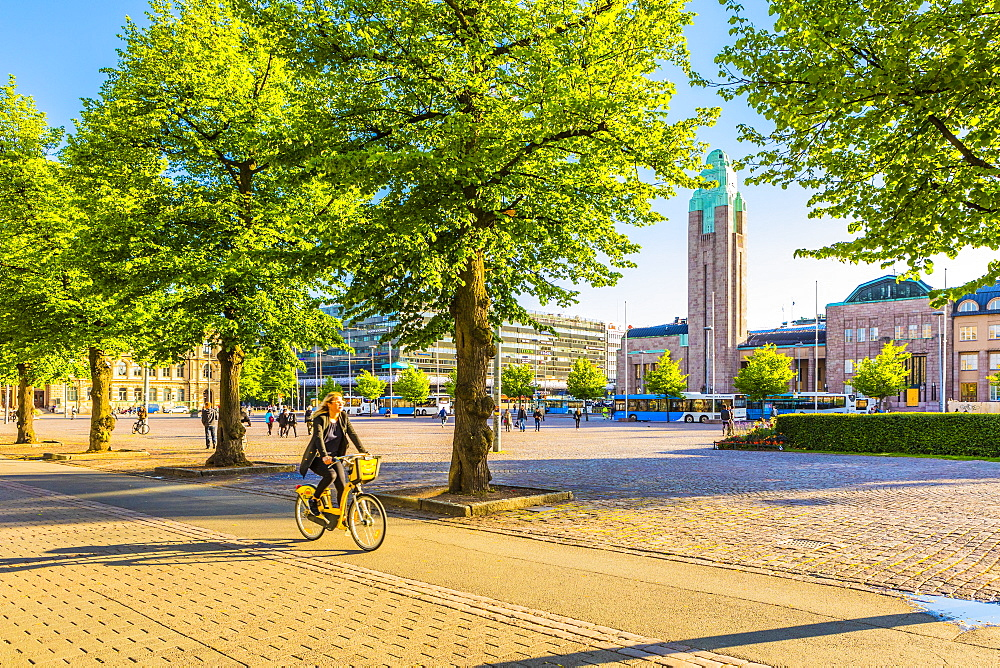 A woman cycling in Helsinki with Rautatieasema Train Station in the background, Helsinki, Finland, Scandinavia, Europe