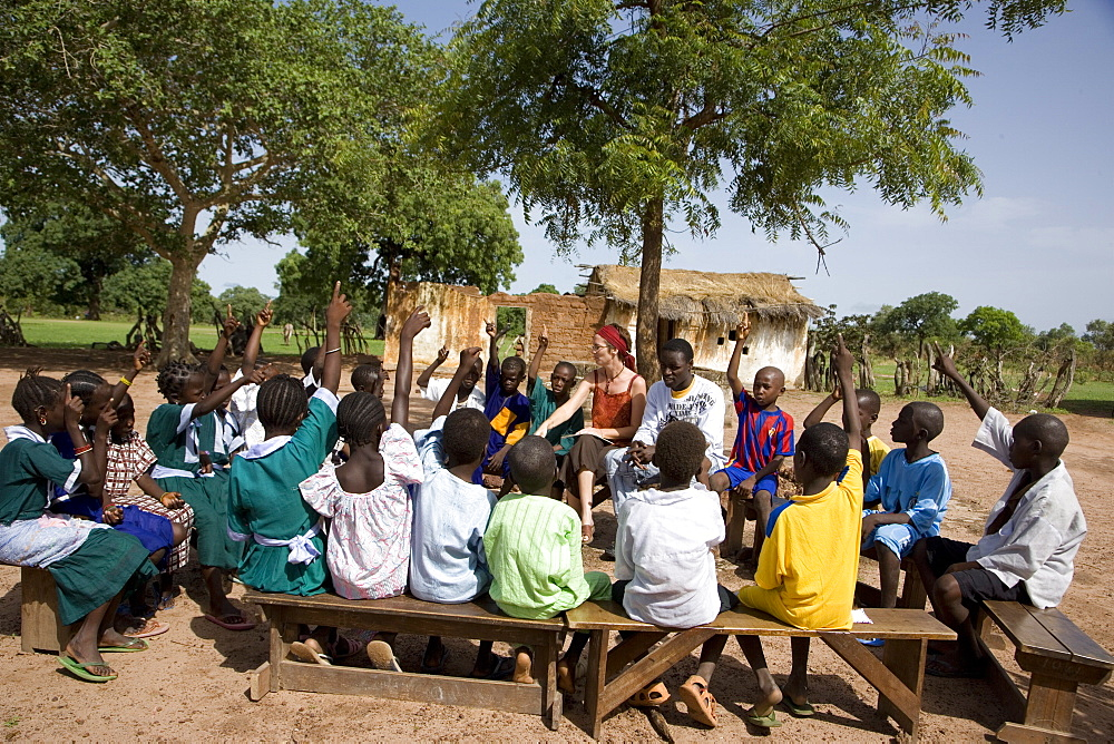 Volunteer Primary Cluster Teacher trainer, Fiona Stevenson leading story time and singing in the yard of primary school in Fori, next to trainee Alpha Ajallow,  The Gambia, West Africa, Africa - 1211-11