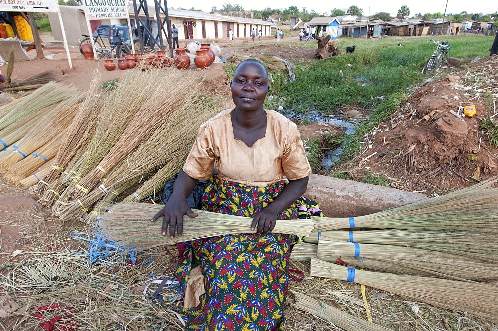 Woman selling home-made brushes by the side of the road, Lira, Uganda, Africa