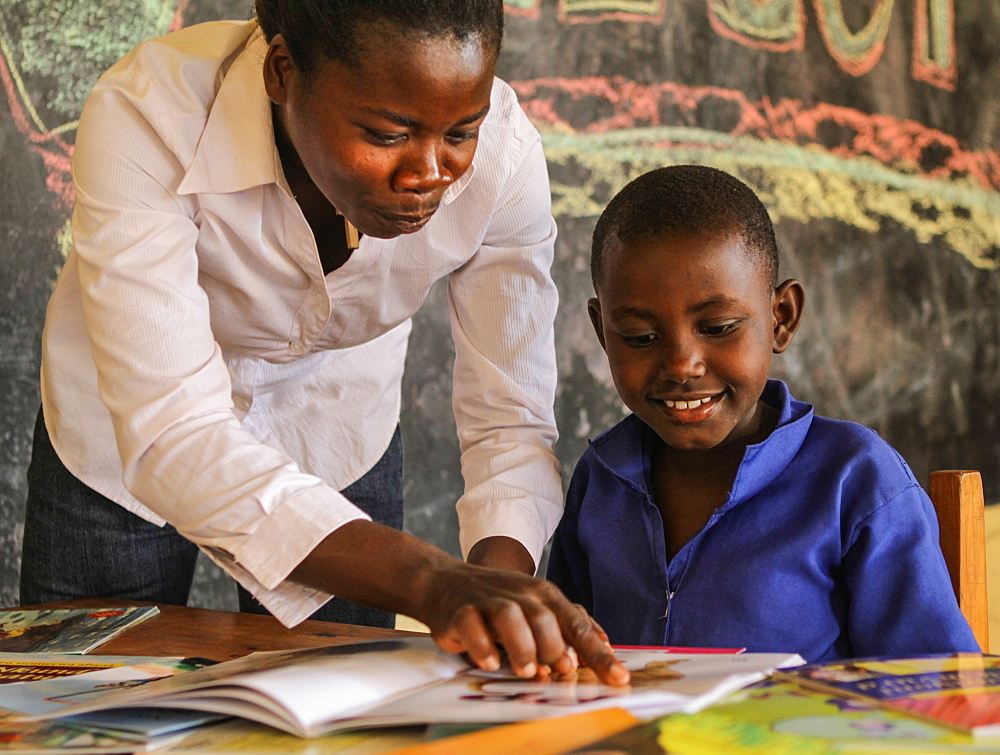 Alice Isingizwe 8 years old who is dumb and her teacher Musabyemariya Alphonsine from Ngwino Nawe, the village for children with disability, teaching Alice how to read a book using signs, Rwanda, Africa - 1211-53