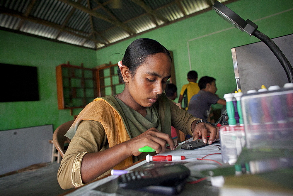 Habiba Akhter, aged 18, a member of a youth club in Afcalpur village, repairing mobile phones, Rangpur District of North West Bangladesh, Asia - 1211-81
