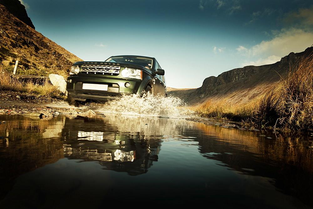 Land Rover splashing through a flooded track, Republic of Ireland, Europe