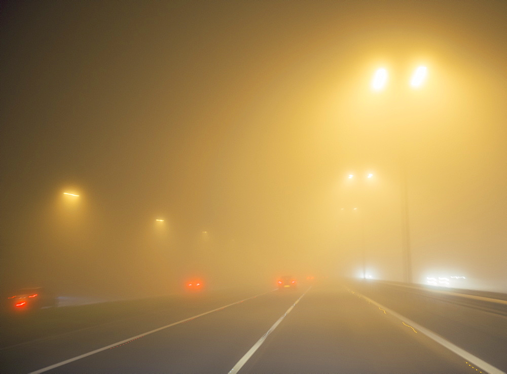 Motorway traffic in thick fog at night, United Kingdom, Europe