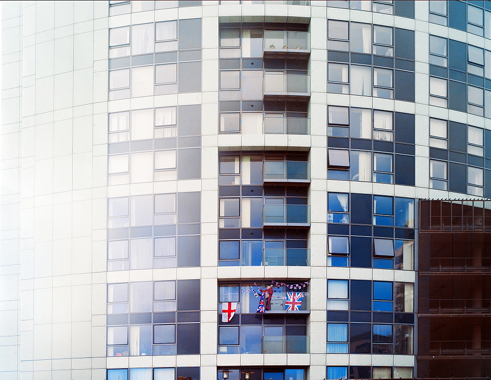 A patriotic woman waves flags from her balcony in a block of flats, United Kingdom, Europe