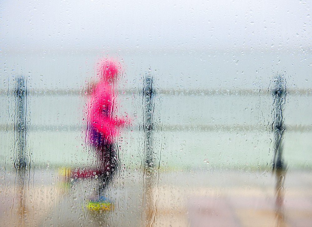 runner braving the elements on a winter seafront run, West Kirkby, Wirral, England, United Kingdom, Europe - 1212-345