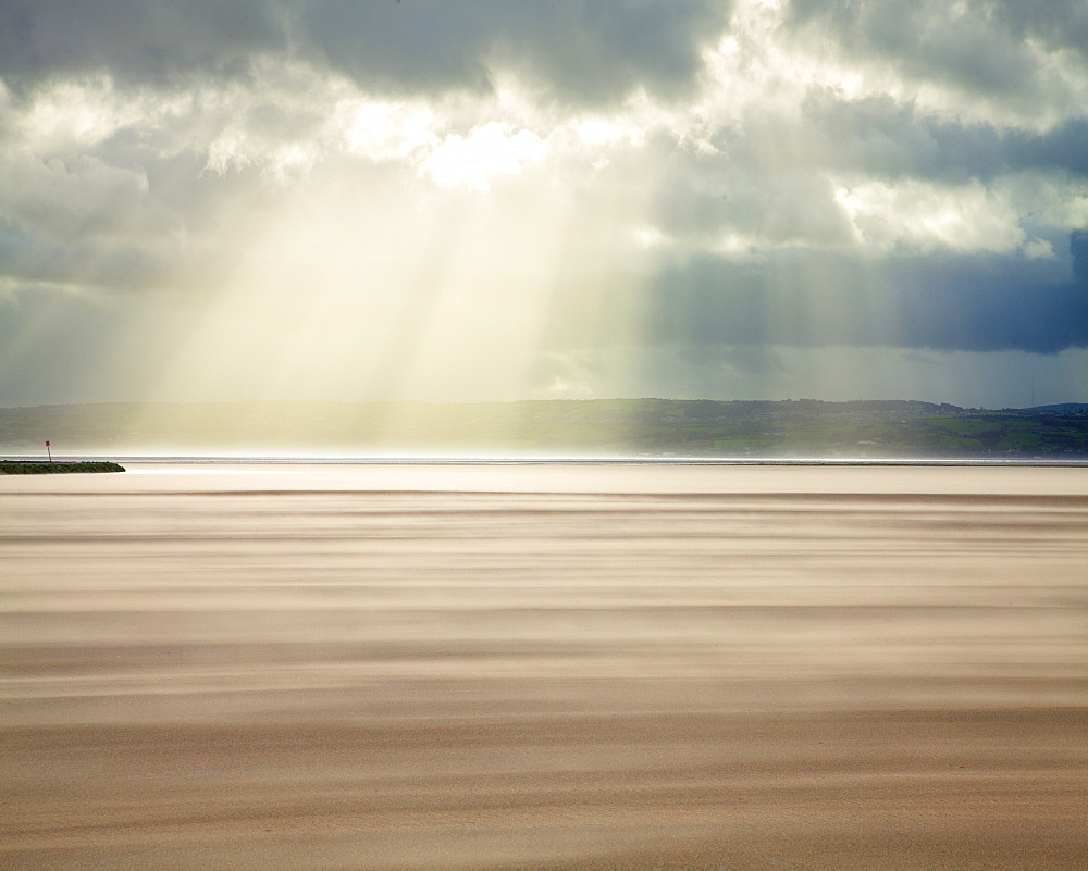 Crepuscular rays through a stormy sky while shifting sands create a cloud underfoot as wind whistles across the beach, West Kirkby, Wirral, England, United Kingdom, Europe