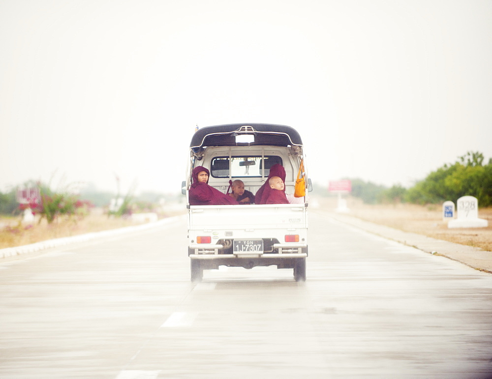 Buddhist monks travelling in the back of a pick up on a modern highway, Myanmar (Burma), Asia - 1212-415