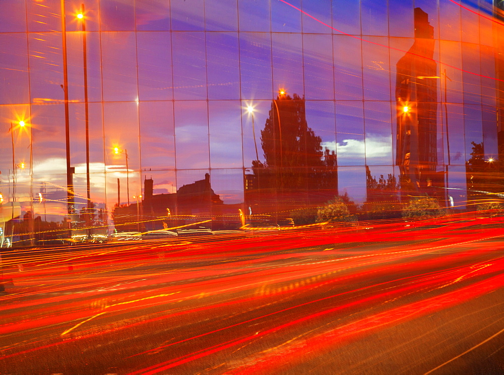 Car tail lights streaming past mirrored building, Liverpool, Merseyside, England, United Kingdom, Europe