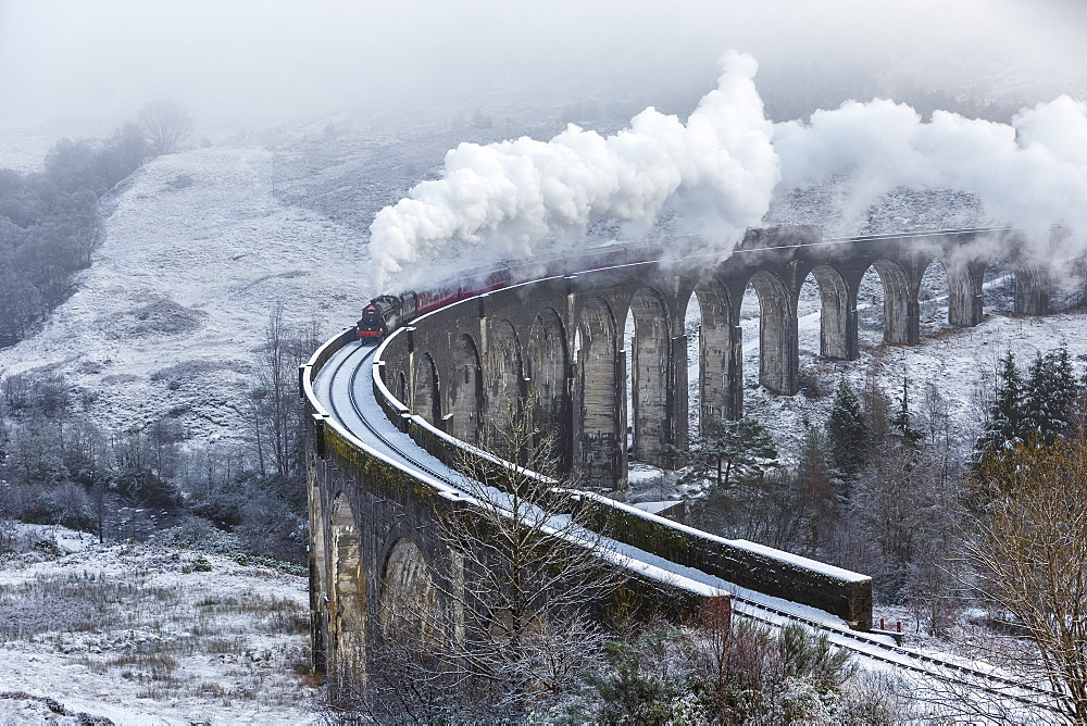 A wintery scene of the Glenfinnan Railway Viaduct with steam locomotive, Highlands, Scotland, United Kingdom, Europe