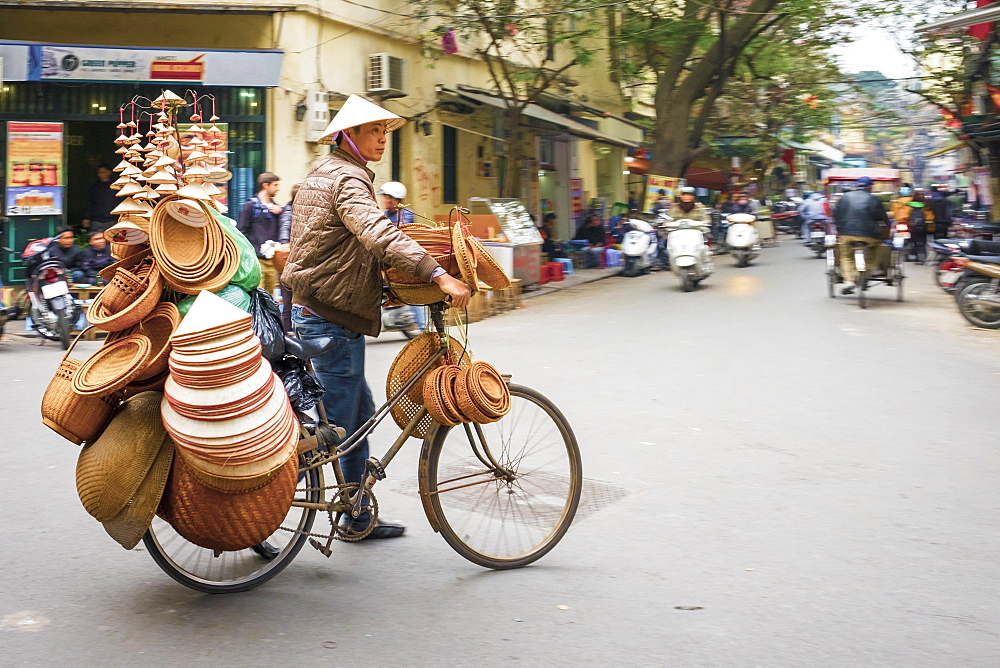 Man on bicycle selling Vietnamese hats in Old Quarter, Hoan Kiem District, Hanoi, Vietnam, Indochina, Southeast Asia, Asia