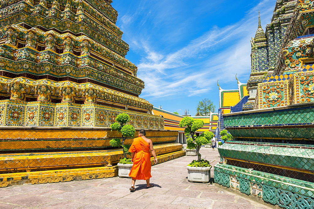 A monk walks past stupas at Wat Pho (Temple of the Reclining Buddha), Bangkok, Thailand, Southeast Asia, Asia