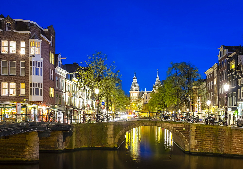 The towers of the Rijksmuseum behind canal houses on the Prinsengracht canal at dusk, Amsterdam, North Holland, Netherlands, Europe