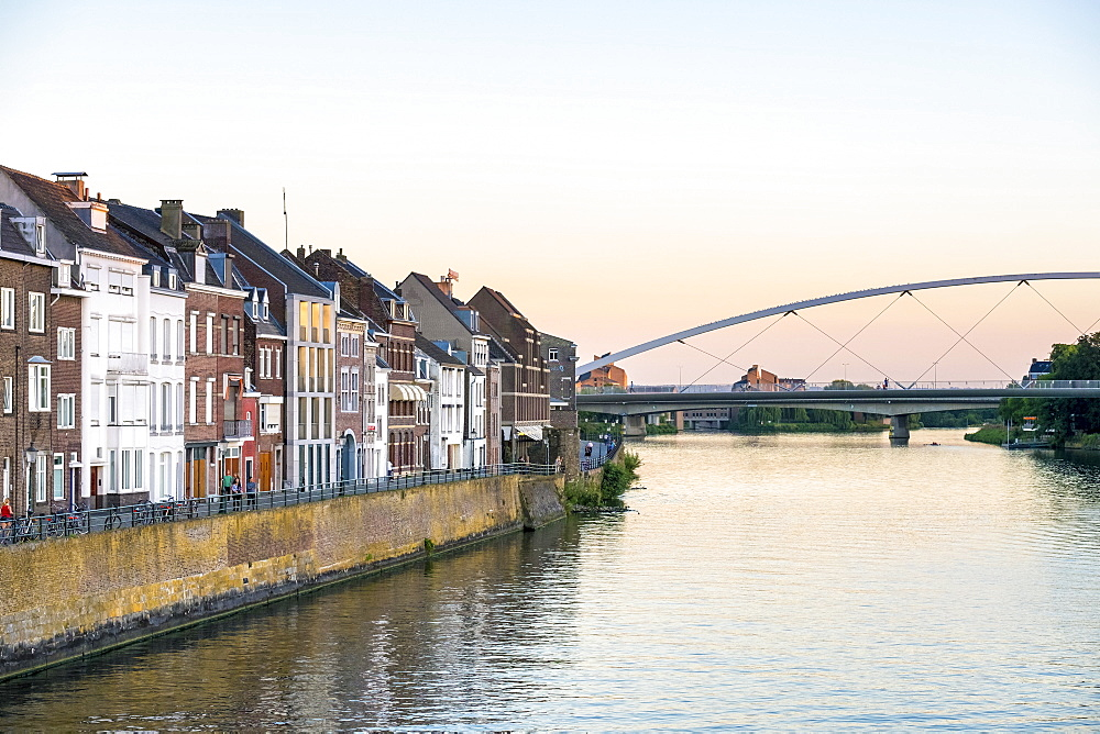 Netherlands, Limburg, Maastricht. Buildings in Wyck-Ceramique quarter and Hoge Brug pedestrian bridge over the Maas River.