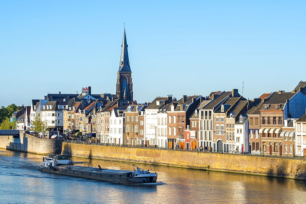Netherlands, Limburg, Maastricht. A boat passes buildings along the Meuse (Maas) River in the Wyck-Ceramique quarter.