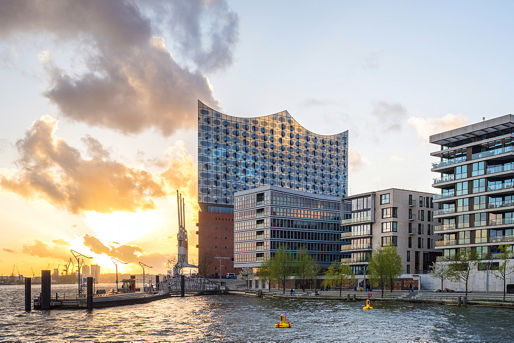 Germany, Hamburg, HafenCity. Elbphilharmonie (Elbe Philharmonic Hall) concert hall and buildings on Grasbookhafen at sunset.