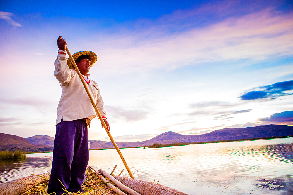 Quechua man rowing a boat on the Floating Grass islands of Uros, Lake Titicaca, Peru