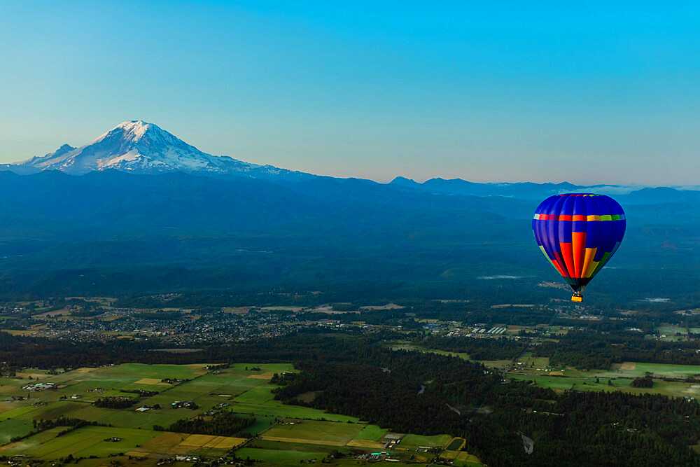 Aerial view of hot air balloon floating over farmland and Mount Rainier in the distance, Washington State, United States of America, North America