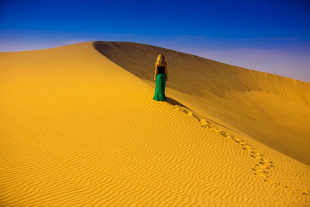Woman standing on sand dune, Huacachina Oasis, Peru, South America