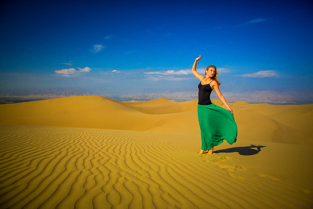 Woman standing on sand dune, Huacachina Oasis, Peru, South America