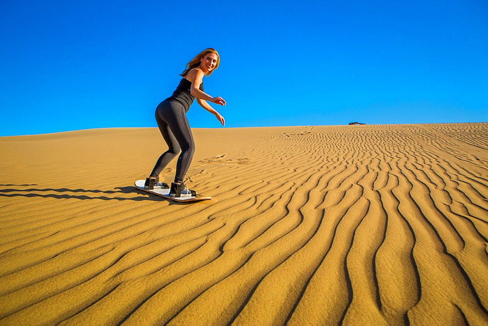Woman sand boarding on sand dune, Huacachina Oasis, Peru, South America