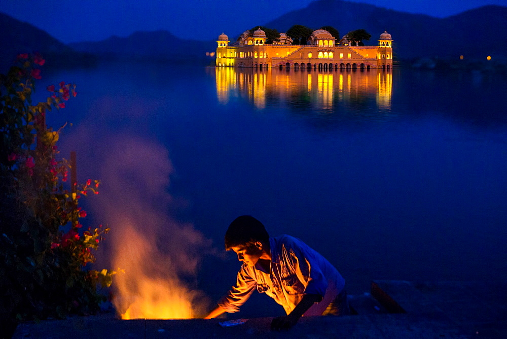 Boy cooking at twilight by the Jal Mahal Floating Lake Palace, Jaipur, Rajasthan, India, Asia