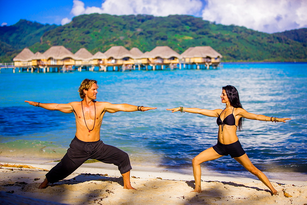 Couple doing yoga in front of overwater bungalows, Le Taha'a Resort, Tahiti, French Polynesia, South Pacific, Pacific - 1218-193