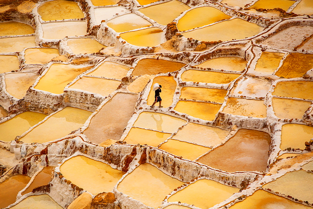 Worker mining for salt, Salineras de Maras, Maras Salt Flats, Sacred Valley, Peru, South America