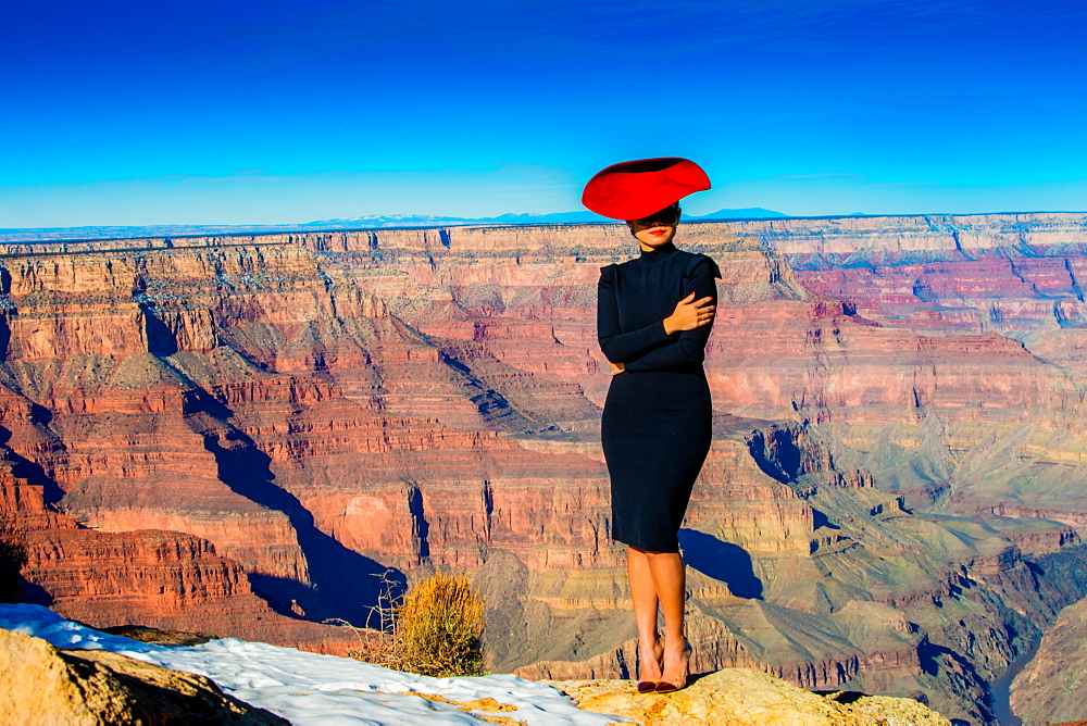 Woman in a red hat posing on the edge of the Grand Canyon, UNESCO World Heritage Site, Arizona, United States of America, North America