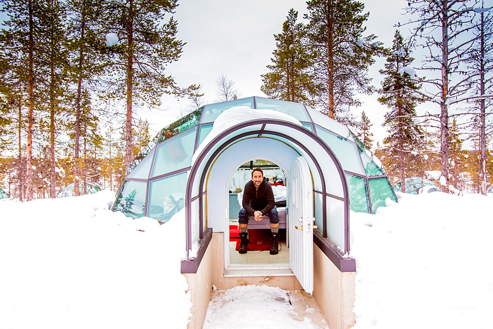 Man sitting inside igloo, Kakslauttanen Igloo Village, Saariselka, Finland, Scandinavia, Europe