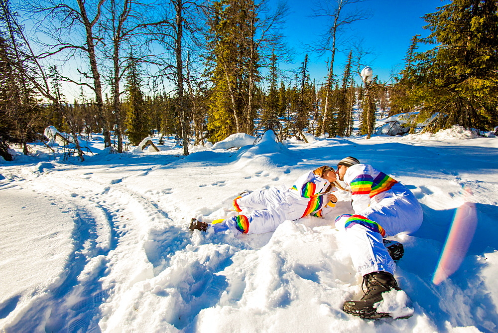 Couple kissing in matching Rainbow Ski Suits, Kakslauttanen Igloo West Village, Saariselka, Finland, Scandinavia, Europe