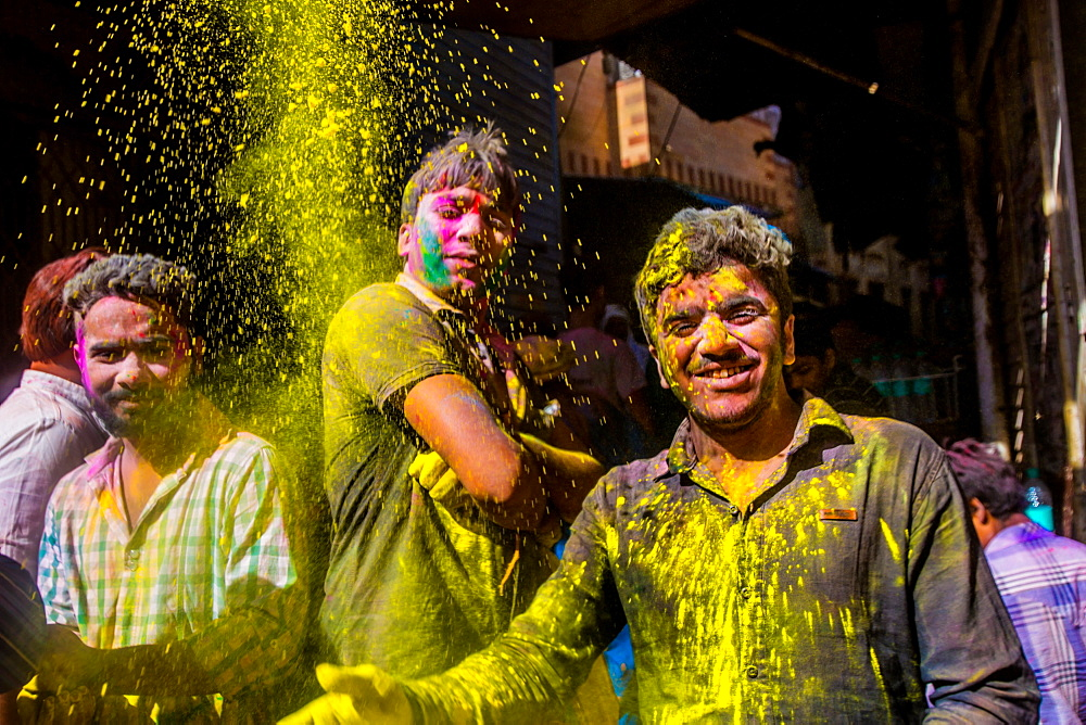 Men throwing yellow pigment, Holi Festival, Vrindavan, Uttar Pradesh, India, Asia