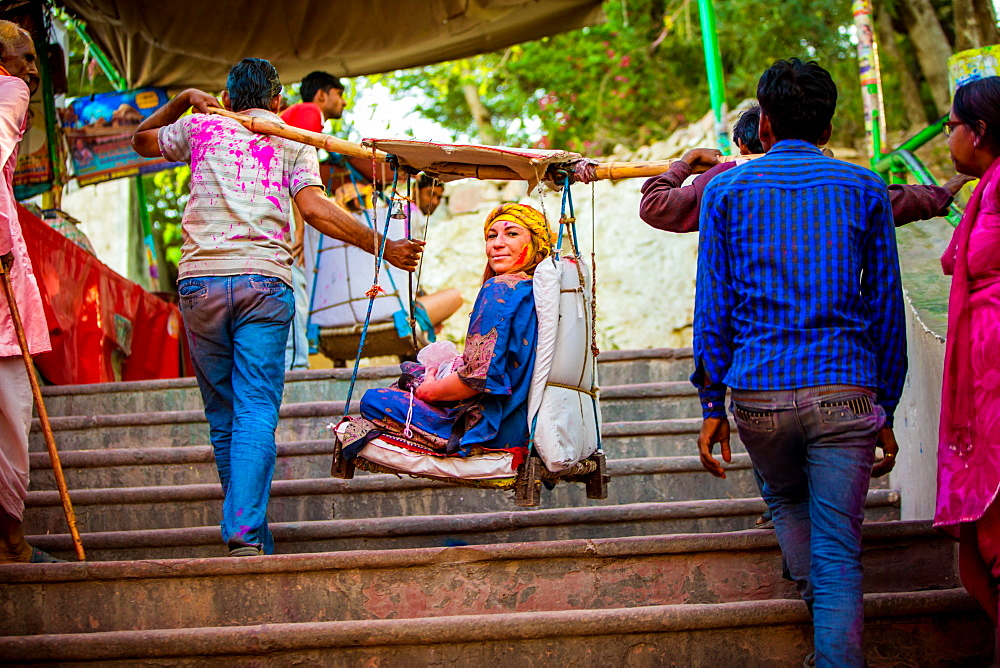 Woman carried in a hanging chair to the temple, Holi Festival, Vrindavan, Uttar Pradesh, India, Asia